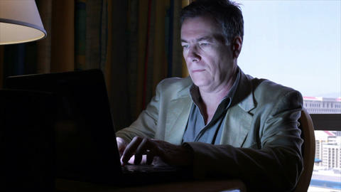 Man typing on laptop in dimmly light room Footage