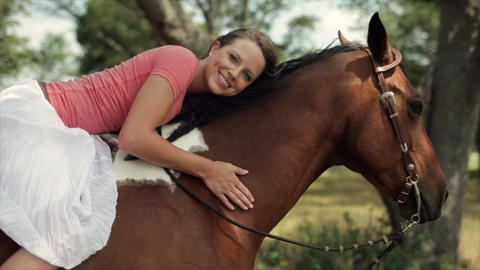 girl laying on her horse Footage