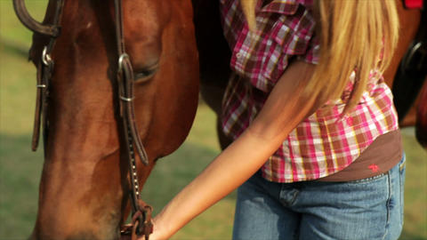 girl putting bridle on horse Footage