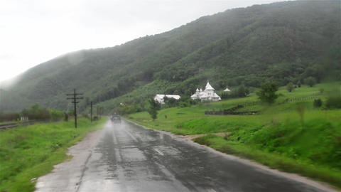 Car traffic in rainy weather on a county road on the wooded hills near the base Footage