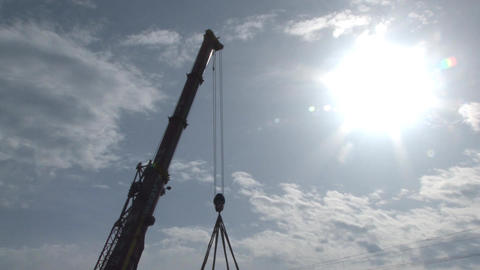 High arm of a crane designed on the sky with fluffy clouds and sun incandescent Footage