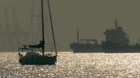 Silhouettes of an unknown anchored sailboat and big cargo ships near Gibraltar 영상물
