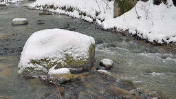 Mountain brook with a boulder at winter time. Slow motion Footage