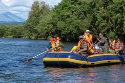 Group of tourists, travelers floating on calm mountain river on raft Fotografía