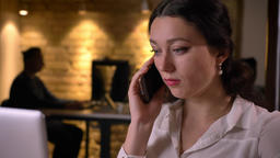 Closeup of young caucasian female office worker making a phone call indoors on Footage