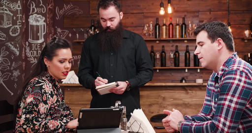Couple ordering to a bearded waiter Archivo