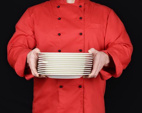 cook in red uniform holds round white empty plates Fotografía