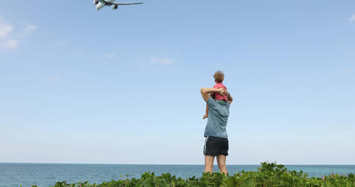 Father with boy on shoulders looking at flying plane ビデオ