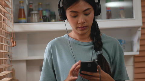 Young asian woman using smartphone inside kitchen at home Footage