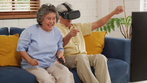 Smiling asian senior couple playing game having fun at home using virtual Footage