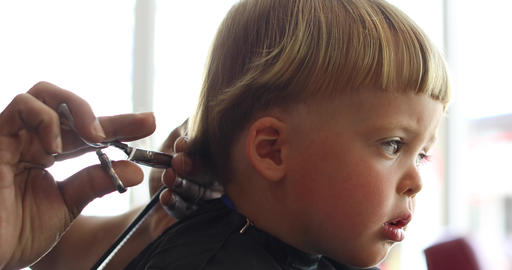 Crop barber doing haircut to little boy Footage