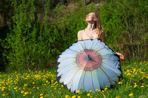 Undressed woman is covered with umbrella in a meadow Fotografía