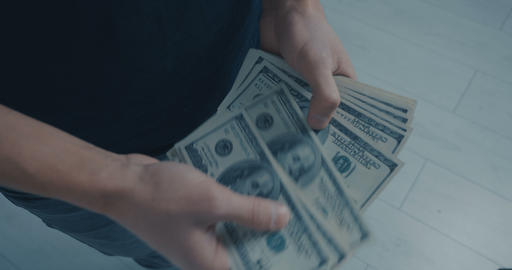 Close-up of young man recounts dollar notes standing in office. Dollars in hand Archivo