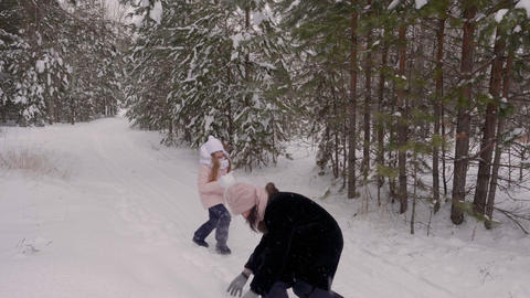 Carefree mom and daughter playing to snow fight in winter forest slow motion Footage