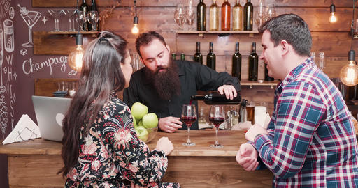 Hipster bearded bartender pouring wine to his clients Live Action
