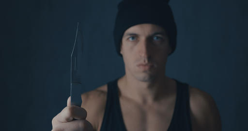 Portrait of Dangerous man in a cap with a knife Footage