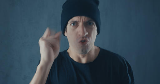 Portrait of angry man in black cap screaming with agression. Threat of violence Live Action