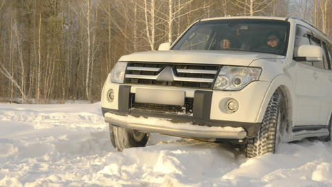 Suv car driving on snowdrift at winter road on snowy forest background slow Live Action