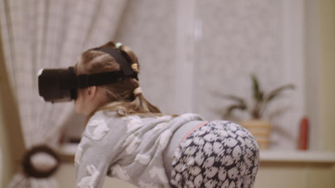 Little girl in VR headset looking up and trying to touch objects in virtual Footage