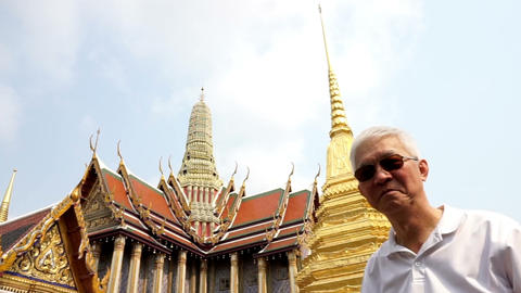 Asian senior man visiting Wat Phra Kaew, Temple of the Emerald Buddha Landmark of Bangkok,Thailand Live Action