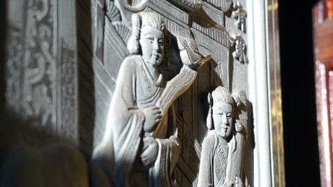 bas relief art work with morning sun light in Chinese temple. Religious art details Live Action