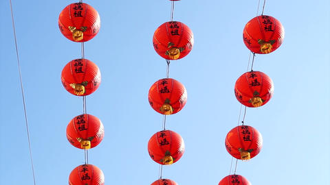 Row of red Chinese paper lanterns with ornate gold patterns and tassels. hanging on wires outside. Archivo