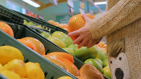 Woman buying fresh exotic citrus fruits at grocery store Stock Video Footage