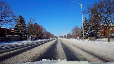 Driving on Snow Covered Road in Day. Driver Point of View POV on Snowy Street in Live Action