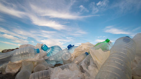 Timelapse. Plastic bottles in a polluted. Clouds background Footage