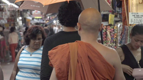 A monk walking in Chinatown in Singapore ビデオ