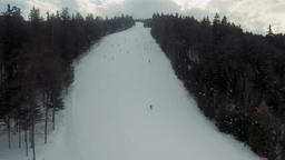 Aerial drone video of skiers going down the sli slope piste in alpine ski ビデオ