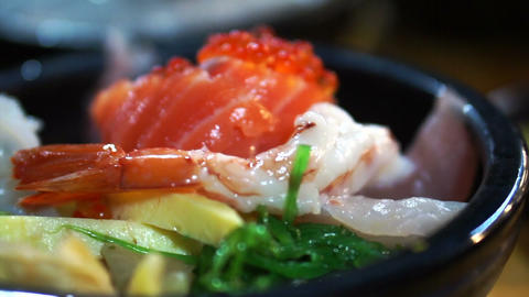 Japanese gourmet sashimi over rice bowl. Chirashi Assorted seafood Live Action