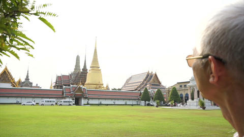 Asian senior man visiting Wat Phra Kaew, Temple of the Emerald Buddha Landmark Footage