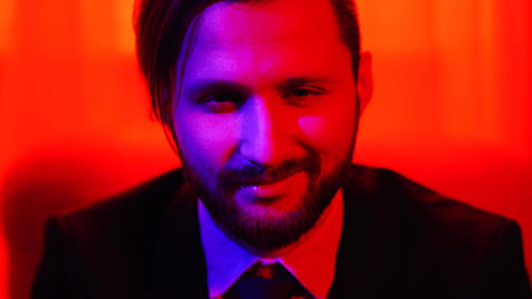 Portrait of bearded smiling man looking at camera isolated over bright red light Footage