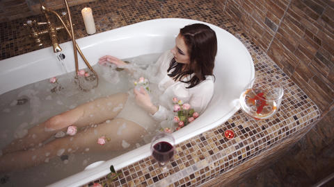 Cute sensual woman in white shirt taking a bath. Water flows from the water tap Footage