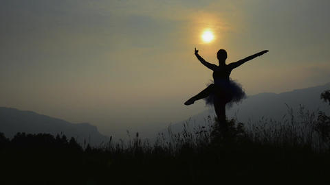 Ballerina in silhouette at sunset in the mountains Live Action