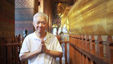 Asian man senior tourist visit Sleeping Buddha, Reclining Buddha statue in Wat Pho of Bangkok, Live Action