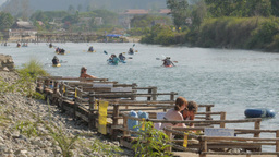Tourists sun bathing with kayaks passing,Vang Vieng,Laos Footage