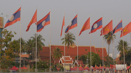 Laos flags in the wind with temple at Vientiane,Vientiane,Laos Footage