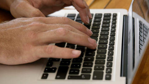 Close up view of masculine hands typing on a laptop Live Action