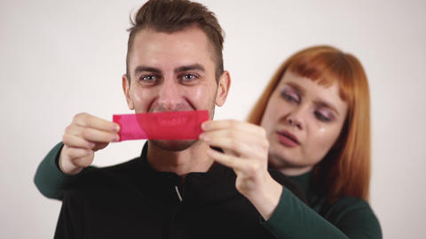 Angry aggressive man yelling and young caring woman tape his mouth with red tape Live Action