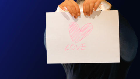 teenage girl holding a paper sign in her hand with a heart drawn above, ripping Footage