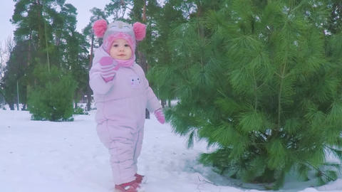 Little girl in the winter forest near the pine tree waving her hand Footage