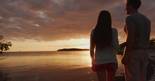 Honeymoon romantic couple in love walking on the beach on orange sunset Live Action