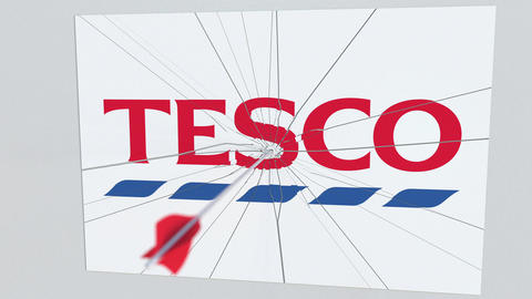 Archery arrow breaks glass plate with TESCO company logo. Business issue Live Action