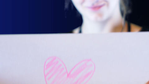 teenage girl holds a paper sign in hand with a heart drawn over it, footage to GIF