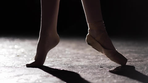 Female foot standing in spotlight on black background in studio. One foot is Live Action