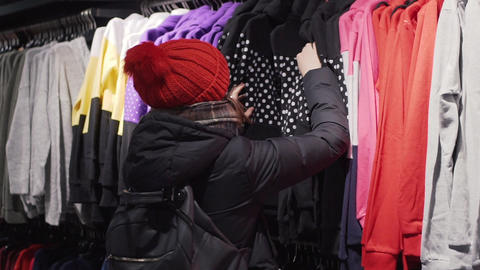 Woman choosing fashion clothes in retail shop in the city mall. Shopping concept Footage