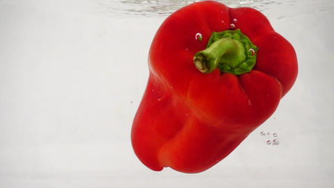 Fresh red bell pepper falls into water with splashes and bubbles Footage