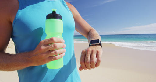 Sport smartwatch - athlete runner using a activity tracker drinking water Live Action